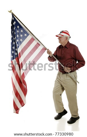 A happy senior patriot wearing a stars and stripes hat while carrying a large  American flag.  Isolated on white.