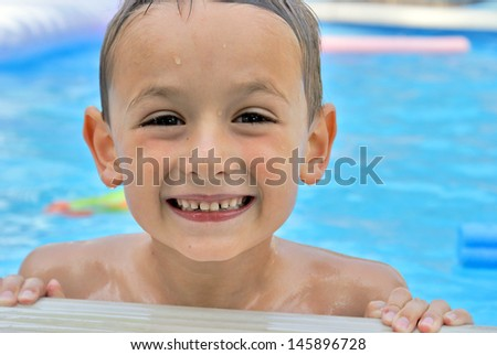 A happy six year old boy enjoys his summertime in the pool.