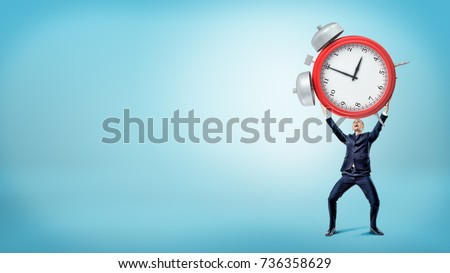 A happy smiling businessman holds a large red alarm clock over his head. Business schedule. Work less hours. Remote management.