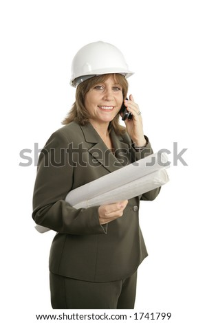 A happy, smiling female architect holding blueprints and talking on her cellphone.  Isolated.