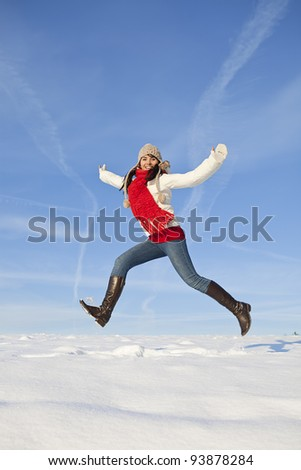 a happy smiling girl jumping on the snow