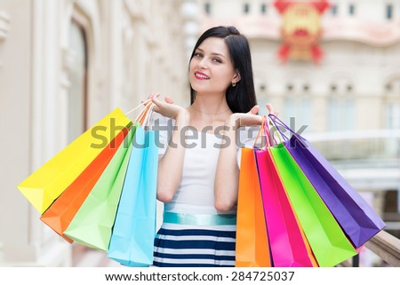 A happy smiling lady with a lot of colourful shopping bags from the fancy shops. Luxury shopping venue.