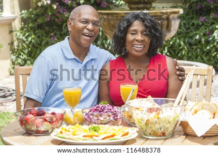 A happy, smiling man and woman senior African American couple eating healthy food at a picnic table outside