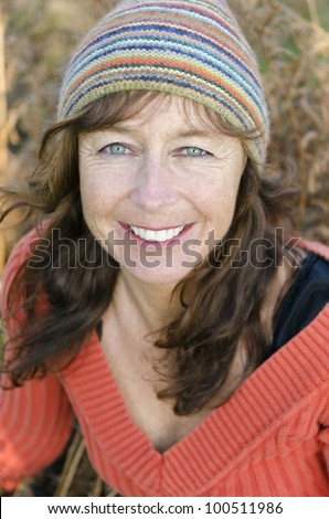 A happy smiling mature woman with freckles and wearing a colorful beanie hat. - stock photo