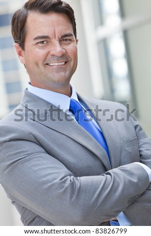 A happy, smiling, smart businessman or man outside in suit, shirt and blue tie with his arms folded