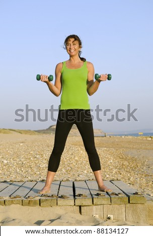 A happy smiling woman in her forties exercising with dumbells on the beach.