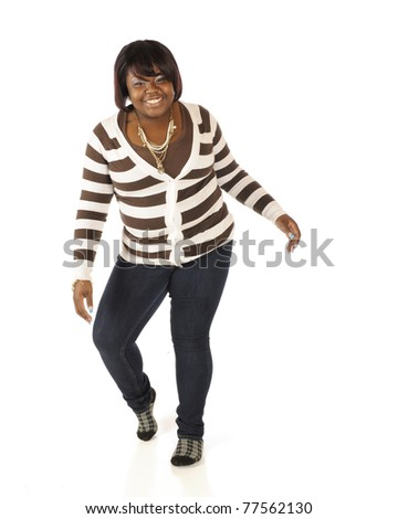 A happy teen girl in broad stripes attempting to do the Moon Walk.  Isolated on white.
