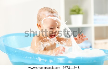 a happy toddler bathing in...
