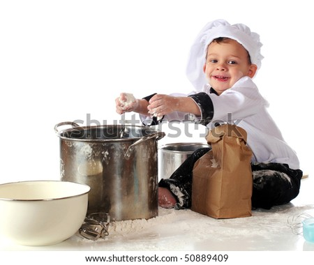 A happy toddler in chef's clothing adding a fistful of flour to a cooking pot.  Isolated on white.