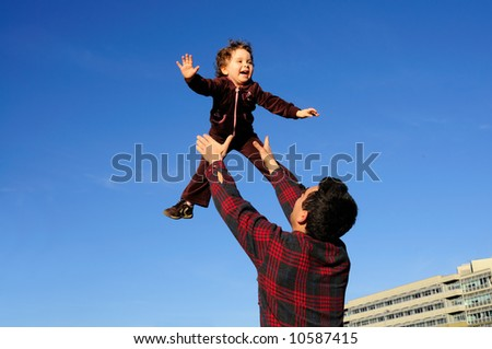 A happy two year old girl tossed into the blue sky by her father.