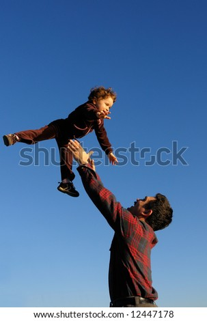 A happy two year old girl tossed into the blue sky by her father - vertical (portrait) orientation.