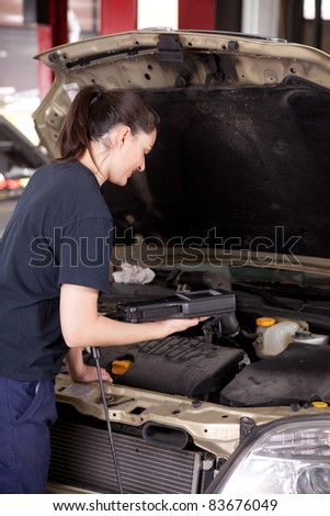 A happy woman mechanic with a smile using an engine diagnostics tool