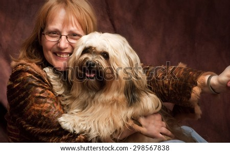 a happy woman with a big smile with her shih-tzu dog in her arm., she is wearing a brown leather jacket