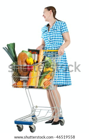 A happy woman with a shopping cart full of groceries on a white background