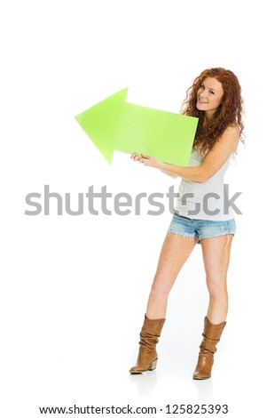 A happy woman with a smile on her face holding an arrow pointing up and left.