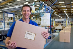 A happy worker holding and showing the final packaged box picked up from the assembly line in a large factory