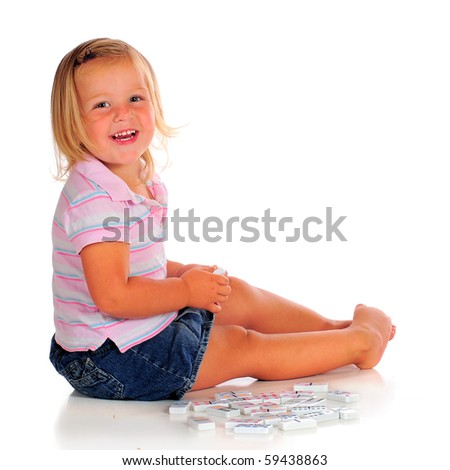 A happy 2 year-old playing with white dominoes.  Isolated on white.