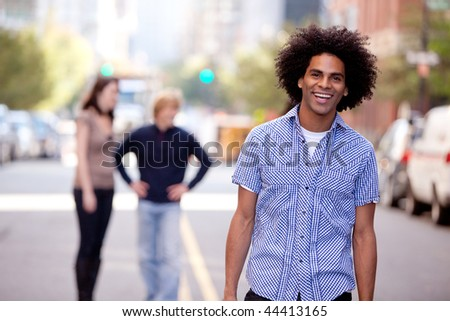 A happy young adult in a city setting with friends