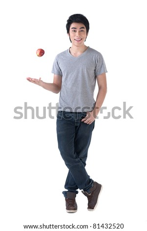 A happy young asian man casting an apple