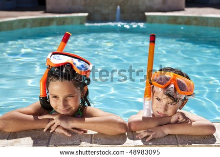 A happy young boy and girl relaxing on the side of a swimming pool wearing orange goggles and snorkel