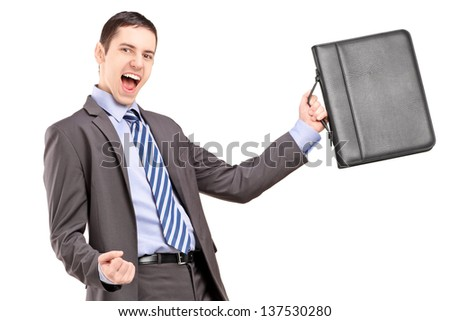 A happy young businessman holding a briefcase and gesturing happiness isolated on white background