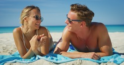 A happy young couple is having fun to apply a sunscreen or sun tanning lotion to take care of their skin during a vacation on a beach.