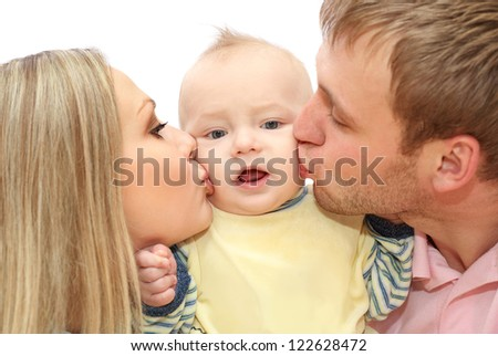 A happy young couple kisses   the baby - stock photo