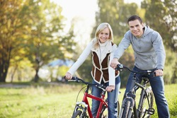 A happy young couple on bicycles in the park