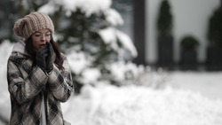 A happy young dark-haired woman in round glasses and a plaid coat walks on a snowy winter day, rubbing her gloved hands against the freezing cold.