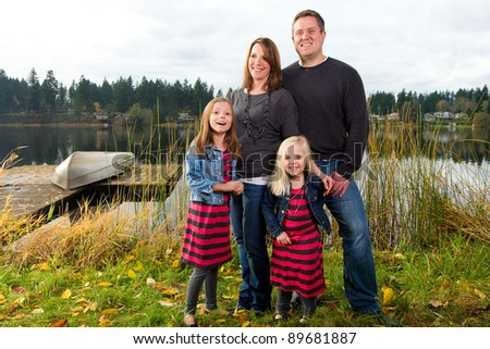 A happy young family outside at a beautiful lake.  A small aluminum boat on a dock is in the background.  Two children, Mom and Dad.