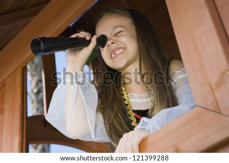 A happy young girl dressed as a pirate peering through telescope from window