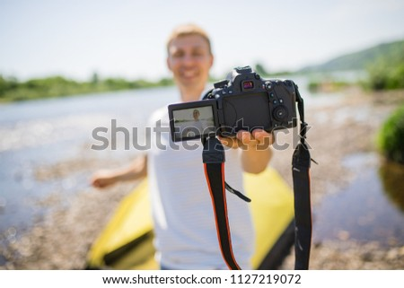 A happy young guy portrait makes a selfie. A cute tourist makes funny photos for a travel blog in nature. on the river bank. the concept of outdoor activities. marketing photographer