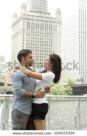 A happy young Indian couple with a Chicago Skyline.