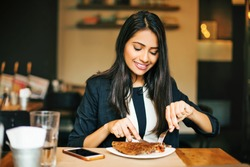 A happy young Indian woman having a pancake in a restaurant