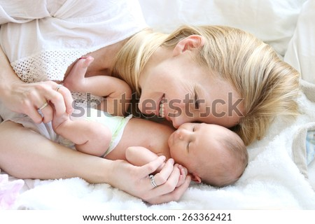 A happy young mother is laying in her white bed, lovingly hugging and snuggling her newborn baby daughter.