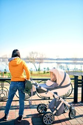 A happy young mother keeps a stroller with a child on the street to the park and looks away. leisure in nature. Sunny weather and beautiful scenery. Healthy lifestyle
