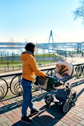 A happy young mother rolls a stroller with a child on the street to the park. leisure in nature. Sunny weather and beautiful scenery. Orange jacket. Healthy lifestyle