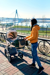A happy young mother rolls a stroller with a child on the street to the park. leisure in nature. Sunny weather and beautiful scenery. Healthy lifestyle