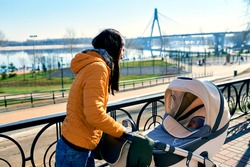 A happy young mother smiles and walks with a stroller and a child on the street to the park. Communication and leisure in nature. Sunny weather. Architecture and nature. Orange jacket. Healthy