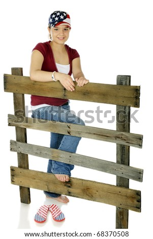 A happy young teen in a stars and stripes hat leaning on an old rail fence.  Isolated on white.
