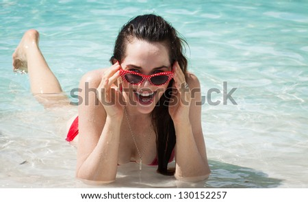 A happy young woman in bikini and funky 50's retro sunglasses lying in the water on the beach looking at camera.