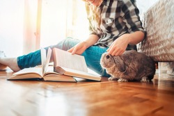A happy young woman sits on the floor and shows a book to a rabbit. Side view. Concept of reading and education