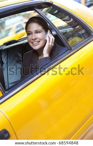 A happy young woman talking on her mobile cell phone in the back of a yellow taxi cab. Shot on location in New York City