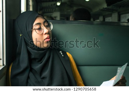 A happy young Young muslim woman sitting next to old vintage train windows looking excited at train ticket. Travelling Backpackers Concept. Selective Focus