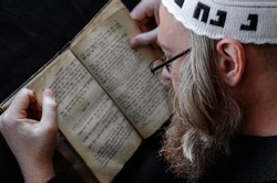 A Hasidic Jew reads Siddur. Religious orthodox Jew with a red beard and with pace in a white bale praying. Closeup