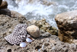 A hat and sunglasses on the beach. The rocky shore. Tropical vacation and relax travel concept.  Mediterranean sea, Turkey. Forgotten things. The reflection in the glasses.