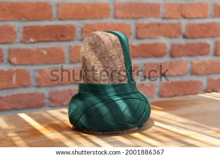 A hat made of felt worn by the whirling dervishes. The brown hat worn by the Mevlevi dervishes. There is a brick wall in the background. Stock photo ©