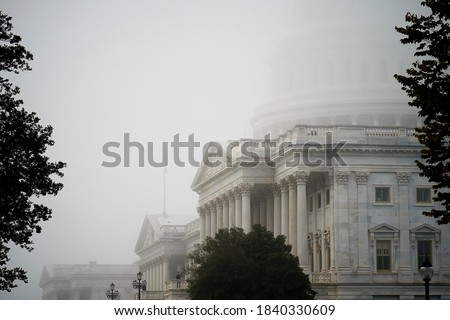 A hazy and blurry photo of the US Capitol building on a foggy morning where only some parts of the building is visible. The fog created a blurry mysterious look and camera noise like image. Foto stock ©
