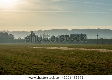 A hazy morning softens hills to silhouettes and farm buildings to profiles with a long view of a field in the foreground.
