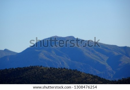 A hazy mountain backdrop beneath a pale blue sky; Tonto National Forest in Arizona